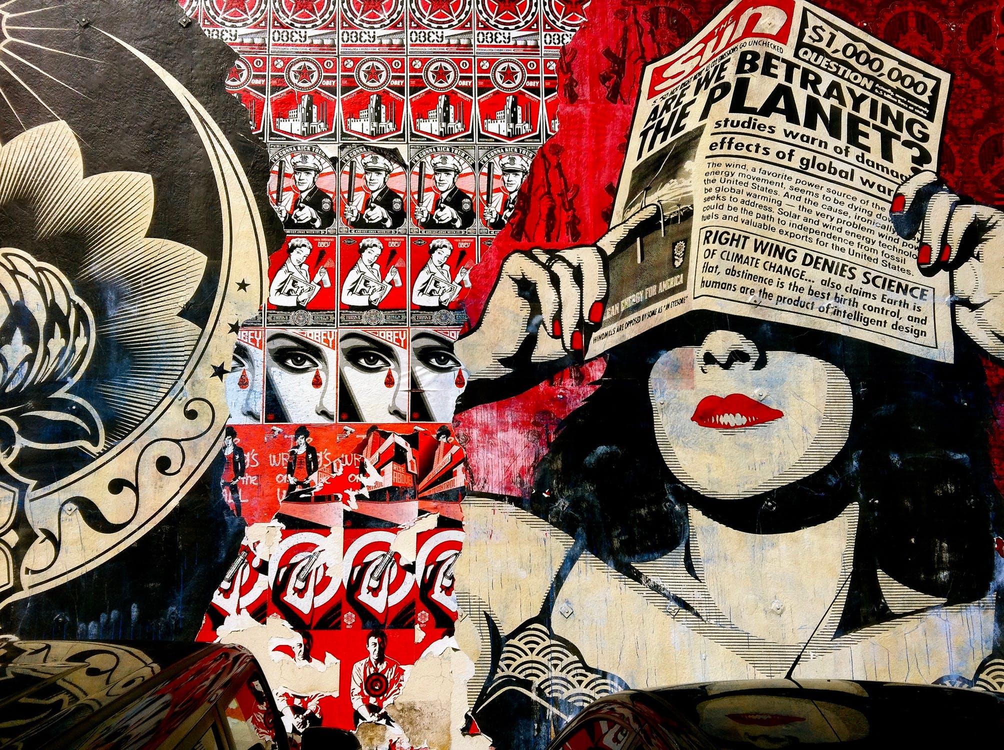Frau hält sich Boulevardzeitung vor die Augen. Im Hintergrund viele Propagandaplakate.